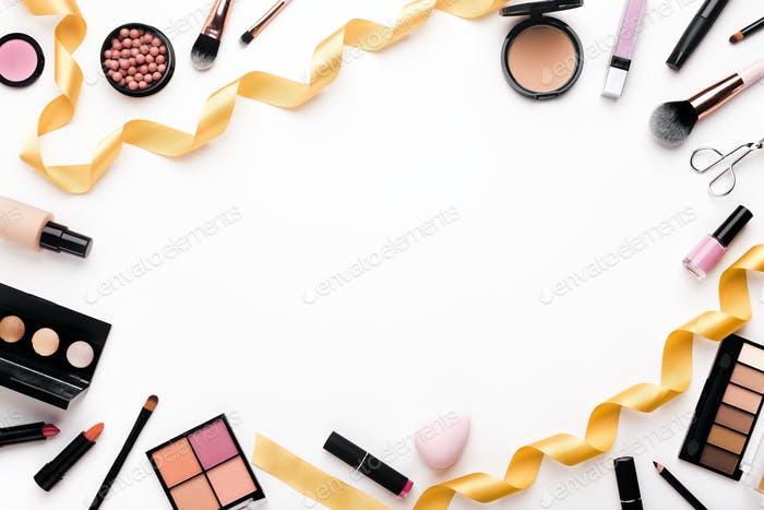 Flat lay background with female cosmetics and golden party ribbon