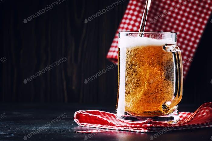 Zwei Gläser deutsches leichtes Bier, Bier in Becher gegossen