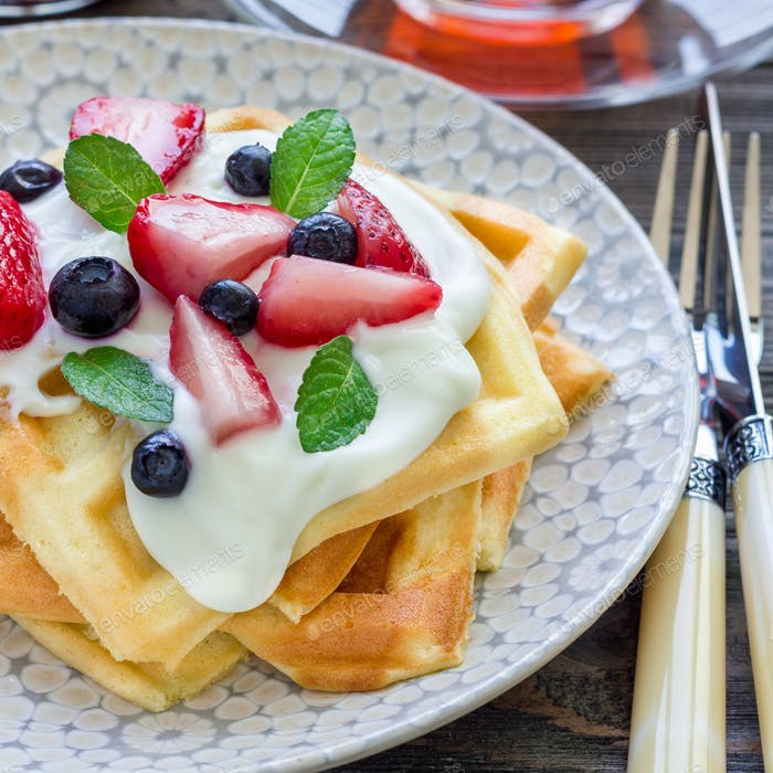 Homemade belgian waffles with yogurt, strawberry and blueberry, breakfast time, square