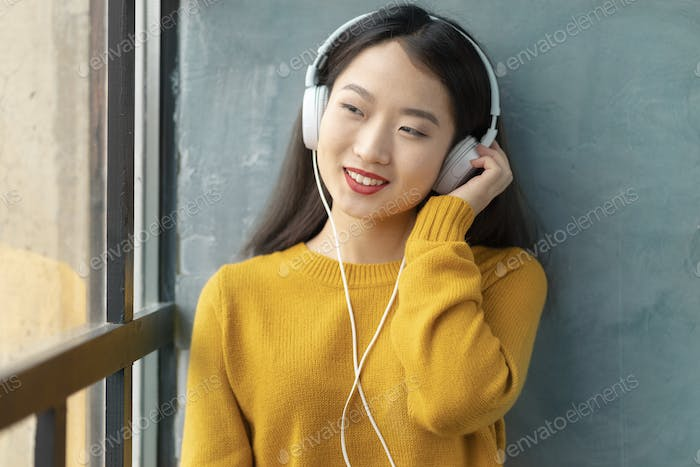 Young beautiful Asian girl listening to music with headphones sitting on window