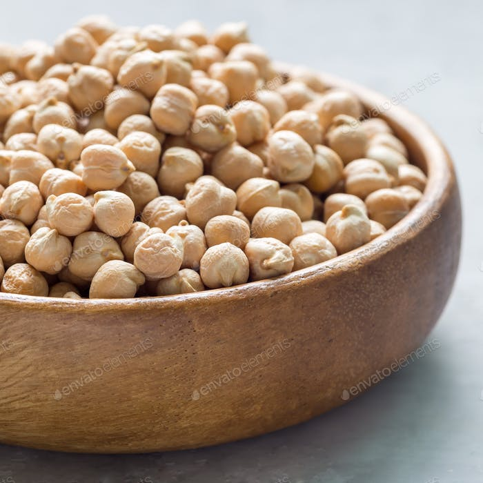 Uncooked dry chickpeas in wooden bowl, closeup, square format