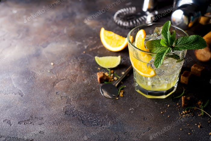 Orange cocktail with ice, leaf of mint and orange slice.