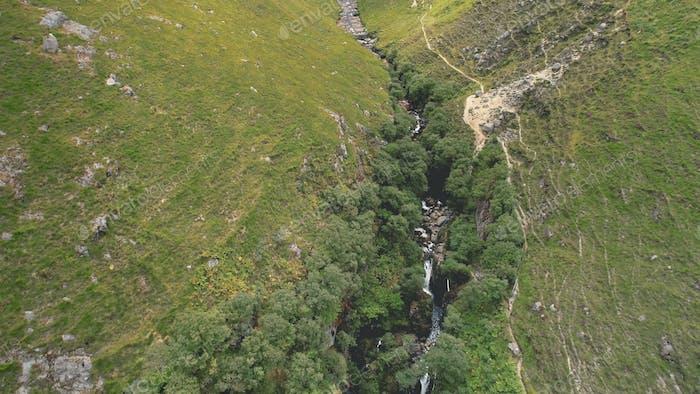 Green Scotland mountains path aerial shot. Narrow rocky way along hillside to cloudy peak