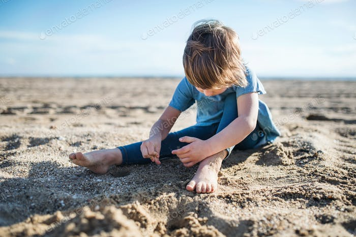 A small girl playing in sand outdoors on beach