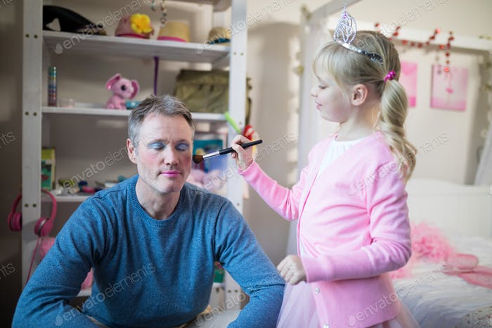 Cute daughter in fairy costume putting makeup on her fathers face
