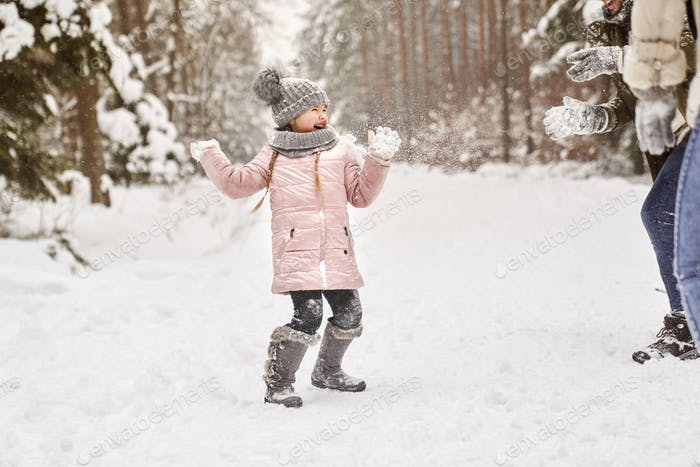Little girl during a snowball fight in the snow