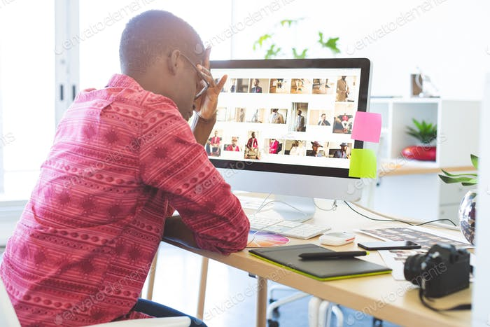 Side view of young African-American graphic designer sitting upset at desk in office