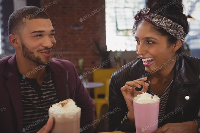 Friends enjoying milkshakes in cafe
