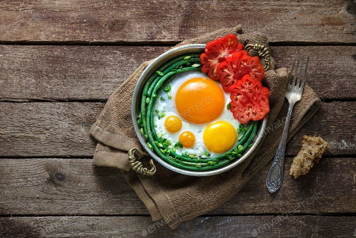 Sunny side fried eggs in a copper pan with tomatoes and green beans, copy space.