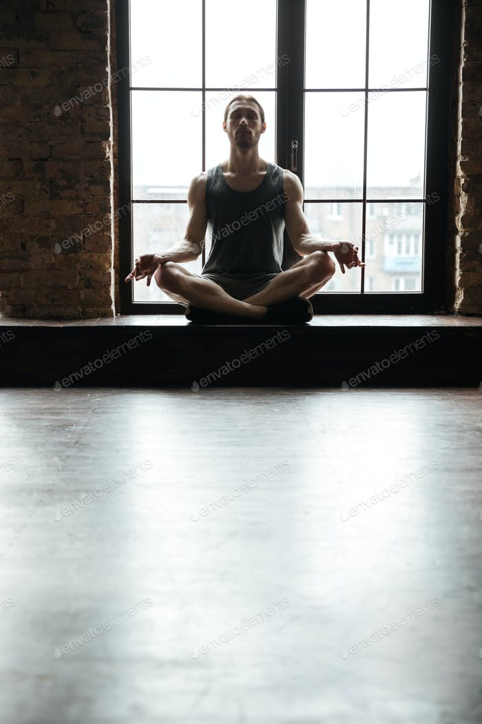 Portrait of a young concentrated sportsman meditating