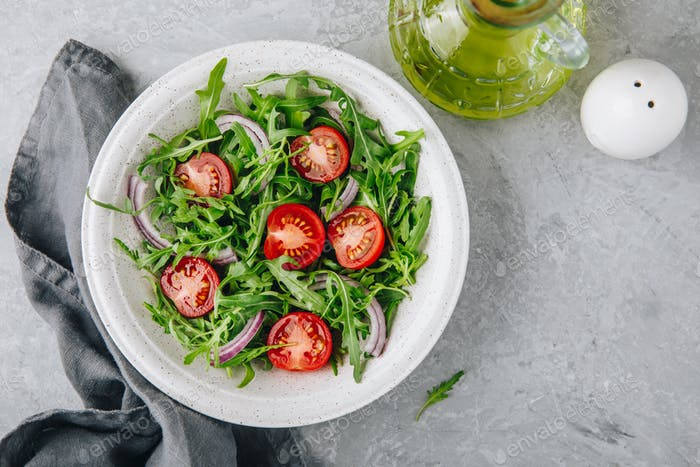 Green salad arugula with tomatoes and red onion in bowl