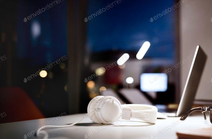 Escritorio de oficina por la Noche con Ordenador y auriculares.
