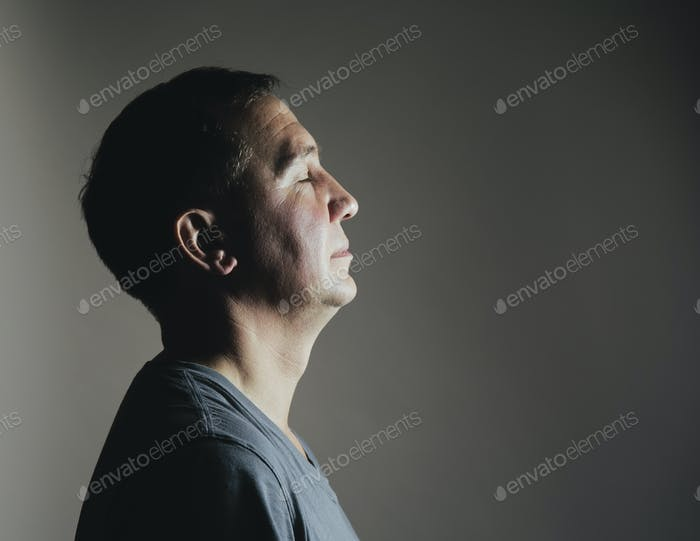 A man sitting still in repose eyes closed, light source shining on his face.