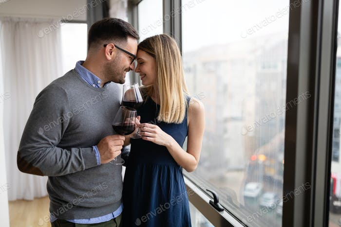 Cheerful happy couple in love drinking wine and having romantic date
