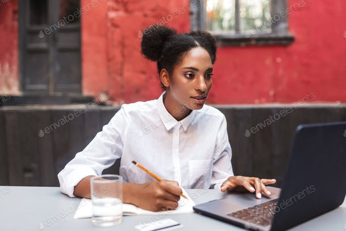 Beautiful african girl in white shirt dreamily working with lapt