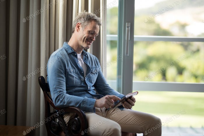 Smiling man using digital tablet on chair