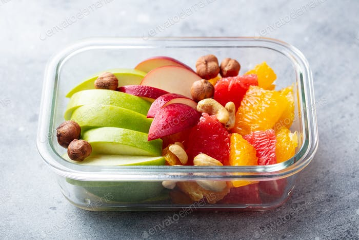 Fruits salad and nuts in a glass container. Healthy eating. Grey background. Close up.