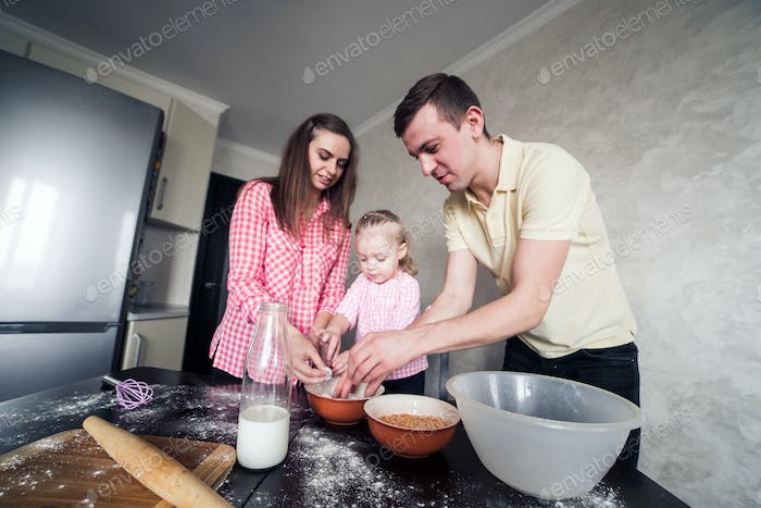 Dad, mom and daughter together in the kitchen