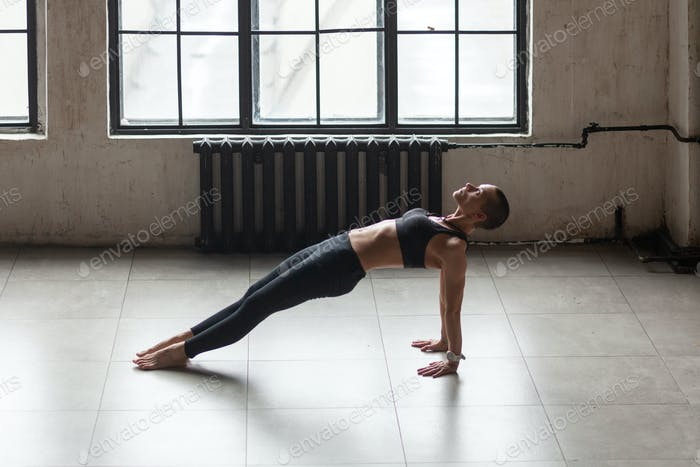 athletic woman doing yoga alone at home