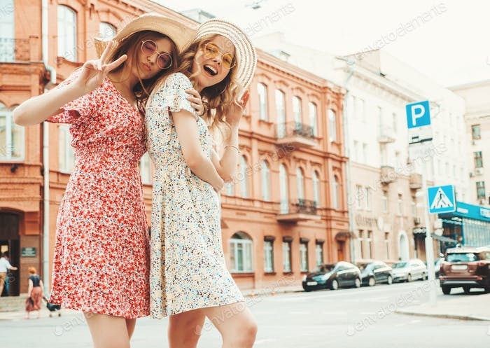 Portrait of two young cute women posing outdoors