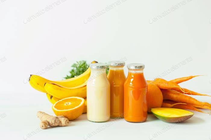 fruit and vegetable smoothies in glass jars, orange mango banana