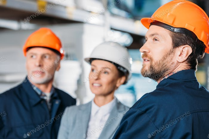 male workers and female inspector in helmets in storehouse