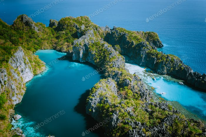 Aerial drone view of Big lagoon surrounded by jagged limestone karst cliffs in morning soft light