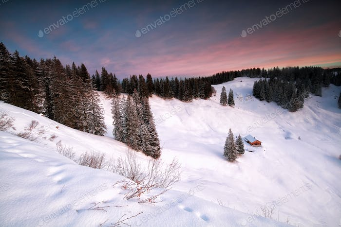 cabin in snowy mountains at sunrise