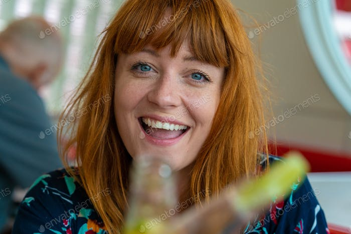 Portrait of ginger girl with blue eyes on a floral dress in a di