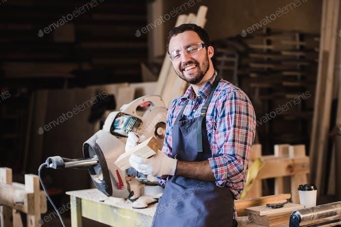 Schöner Zimmermann in Schutzbrille sieht Kamera und lächelnd, während er in der Nähe seines