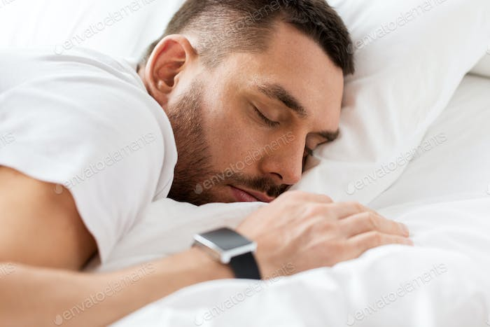 close up of man with smartwatch sleeping in bed