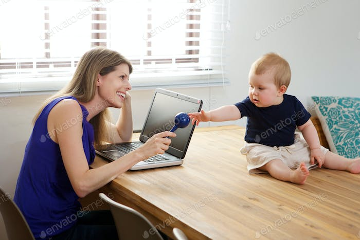 mother sitting at table with laptop and playing with baby boy.