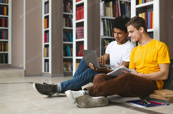 Two friends making homework on floor in campus library