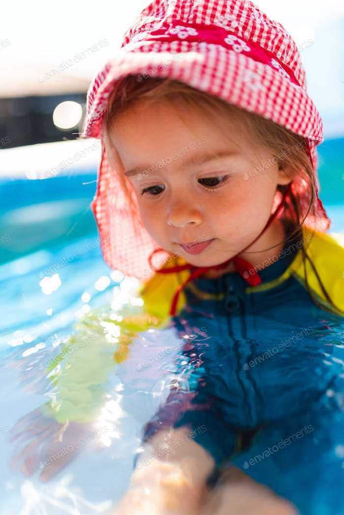 Child in Inflatable swimming pool in backyard