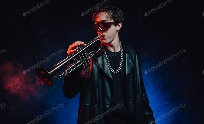 Stylish guy in black leather clothing plays brass in dark background