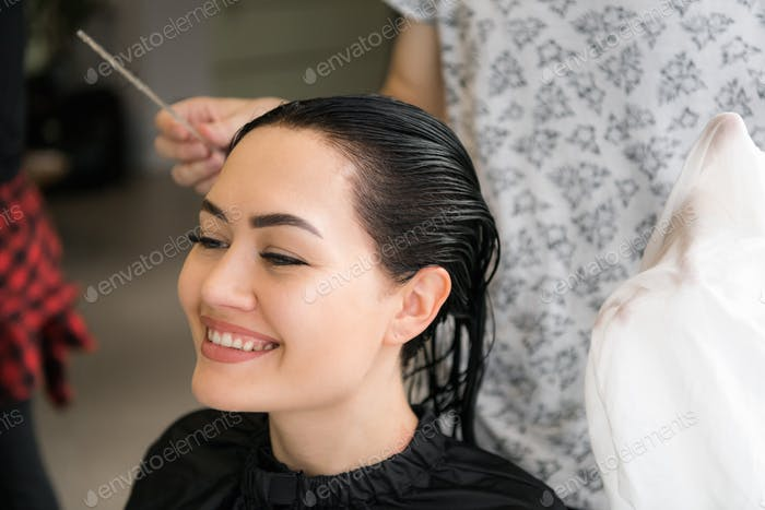 Attractive woman smiling while having a consultation with her hair stylist.