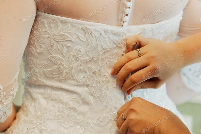 fastening the wedding dress, closeup on hands