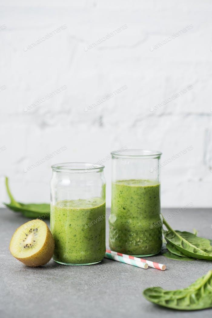 Nahrhafter und gesunder organischer grüner Smoothie in Gläsern