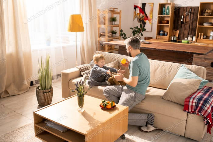 Father playing with son on sofa