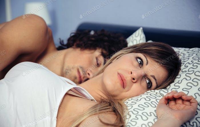 Thoughtful woman lying near her sleeping boyfriend