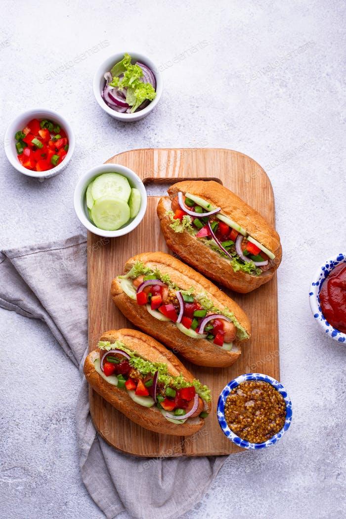 Perros calientes con salchichas, salsas y verduras