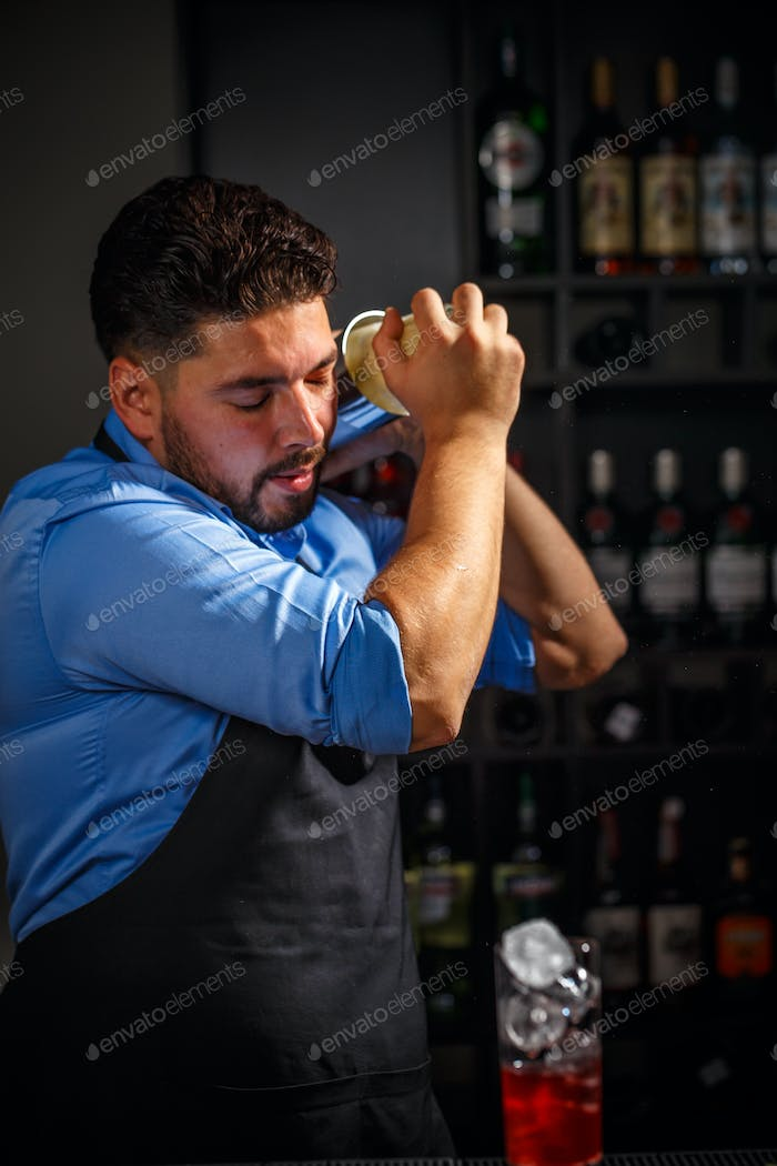 Bartender shakes and mixing alcohol
