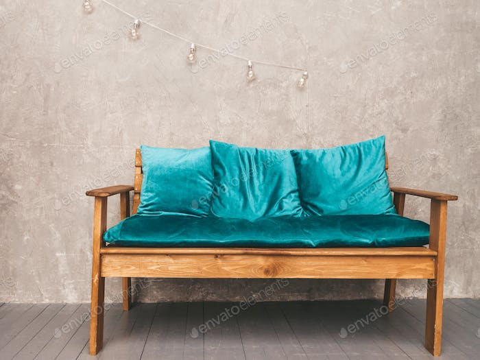 Grey wall interior with stylish upholstered blue sofa