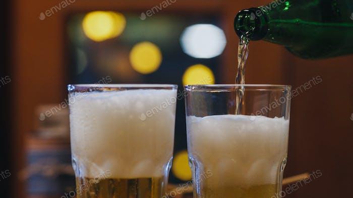 Grupo de turistas jóvenes amigos asiáticos puchando cerveza artesanal en vidrio y teniendo lugar en el club nocturno