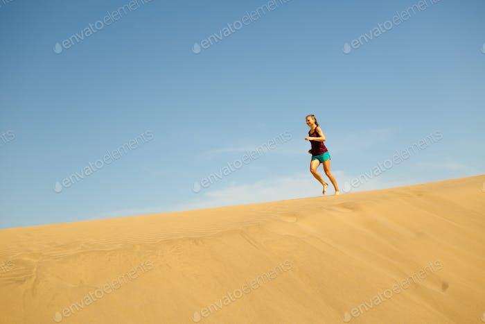 Woman running barefoot on sand desert dunes