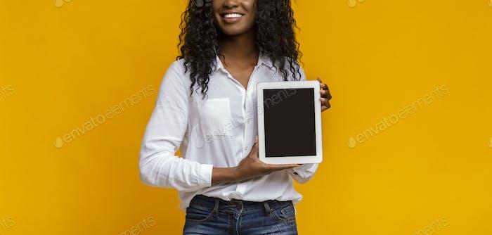Afrikanische Frau zeigt leere digitale Tablet-Bildschirm