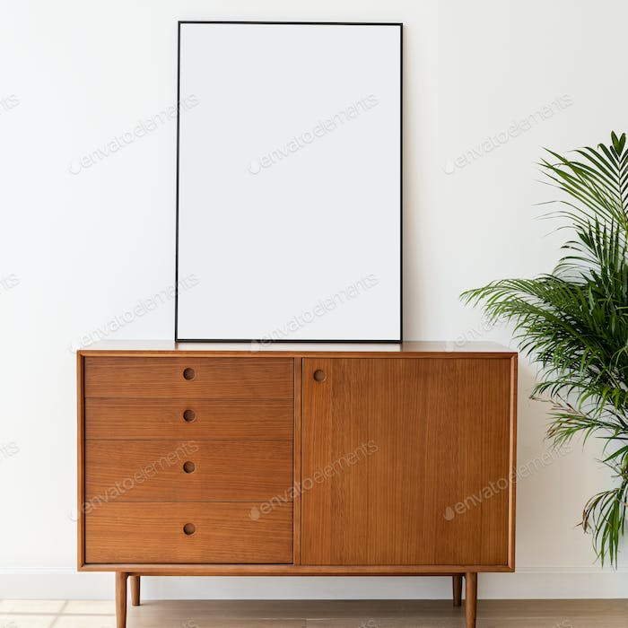 Blank picture frame on a wooden cabinet