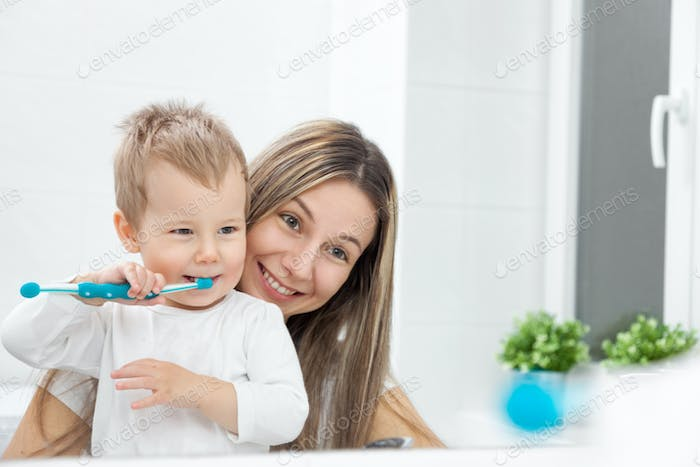 Happy mother teaching her son how to bush teeth