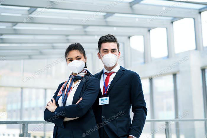 Young flight attendants looking at camera in airport lounge, coronavirus, travel and new normal