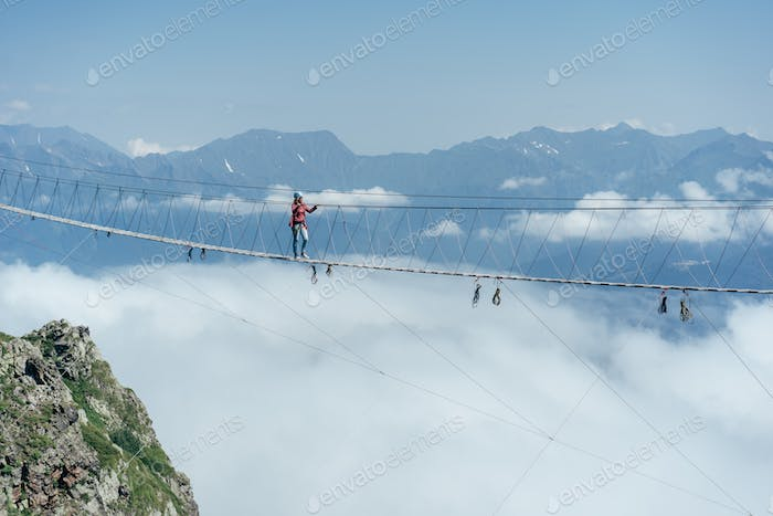 A person walks on a suspended rope bridge in the clouds.